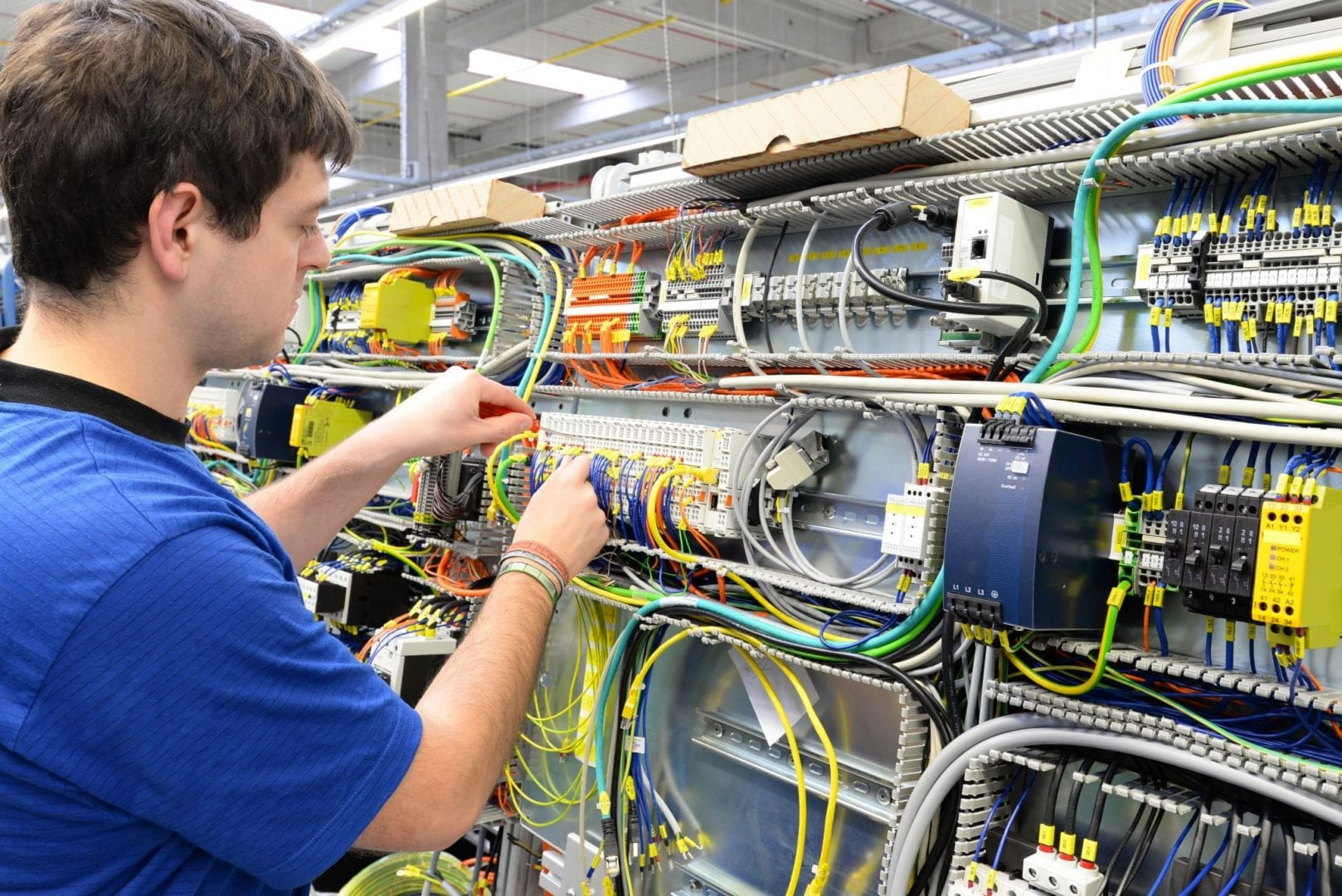 Elektroniker im Maschinenbau montiert Schaltschrank in einer Fabrik // workers mounted electronics in a factory