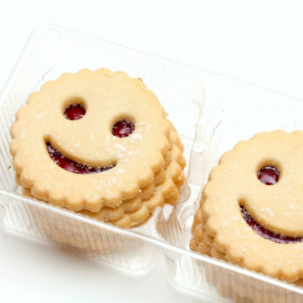 smiling cookies in plastic box isolated on white